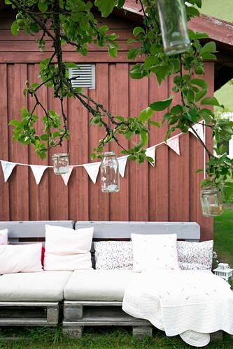 Gemütliche Palettenbank vorm roten Holzhaus im Garten