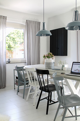 White wooden table and wooden chairs in bright dining room