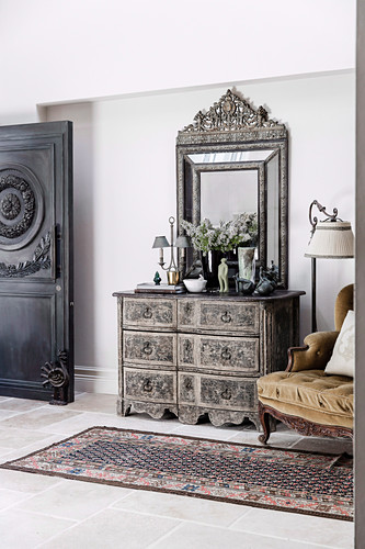 French chest of drawers and mirror in the hallway with antique door