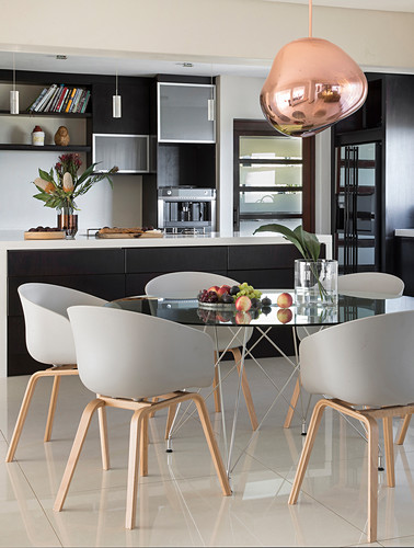 Round glass table and designer chairs in dining area in front of kitchen island