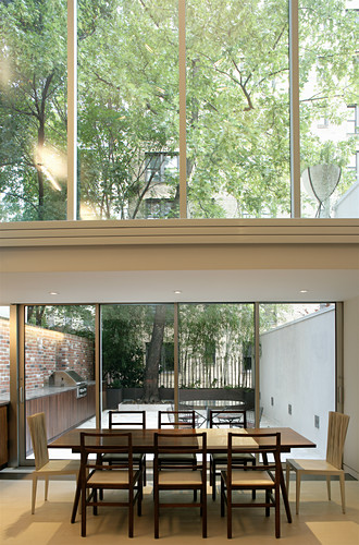 Dining table next to glass wall in narrow, architect-designed house