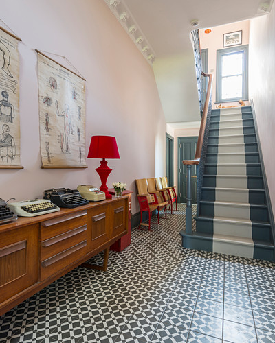 Patterned floor and striped staircase in entrance hall of period building