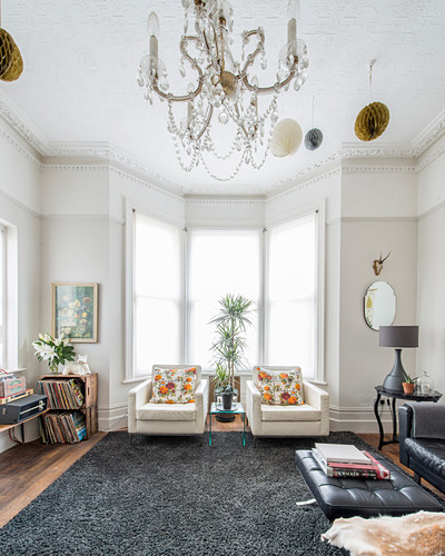 Two armchairs in bay window of living room with stucco ceiling