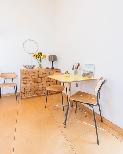 Simple dining area and chest of drawers with carved letters on front