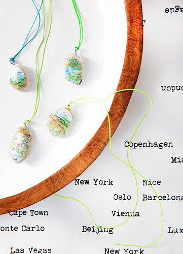 Pendants made from stones covered with sections of maps