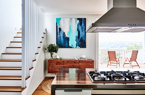 View past island counter with gas hob to sideboard between staircase and balcony