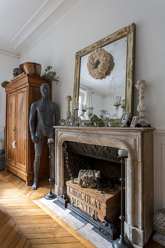 Mirror on mantelpiece above fireplace, sculpture and wooden cupboard in living room