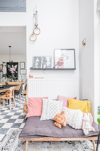 Bohemian cushions on couch next to open doorway leading into dining room