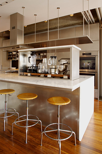 Various kitchen devices on island counter and barstools in elegant, open-plan kitchen