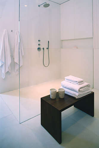Towels and beakers on stool next to shower area with glass screen