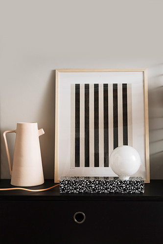 Hand-made designer lamp in front of striped artwork and next to jug
