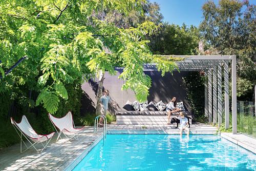 Familie mit Hund am Pool im Garten