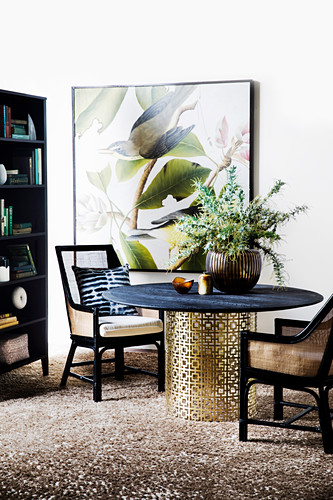 Upholstered chairs around a round dining table with a filigree metal base in front of a bird picture