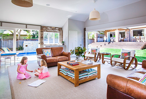 Lounge with leather furniture and glass front, girls playing on the floor