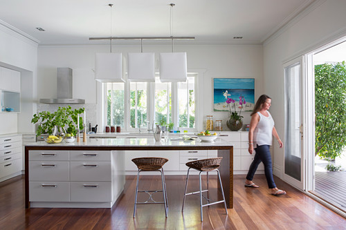 Kücheninsel und Barhocker in offener Küche mit Terrassenzugang, Frau im Hintergrund