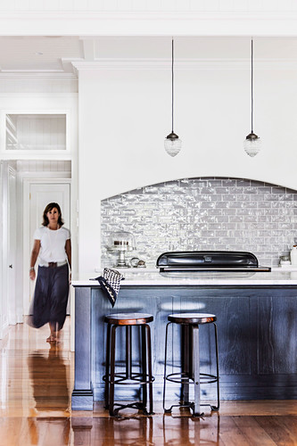 Counter with bar stools in open kitchen, woman in background