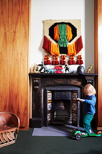 Toddler with scooter in front of an antique fireplace, toy dinosaurs and wall hanging