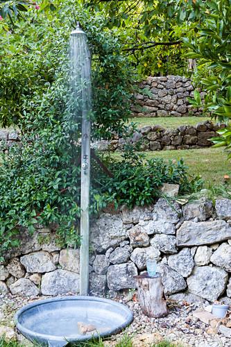 Outdoor shower against stone wall in garden