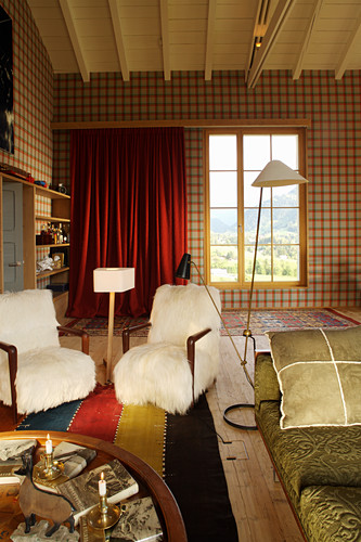 Armchairs and standard lamp in converted loft with tartan wallpaper