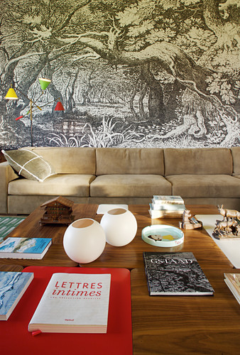 Coffee table and elegant sofa in living room with mural wallpaper