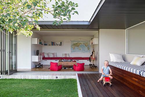 Kind fährt Spielzeugauto auf der Terrasse eines modernen Hauses