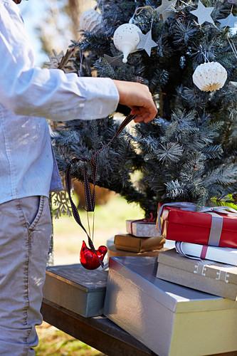Mann schmückt Weihnachtsbaum im Garten bei Sonnenschnein