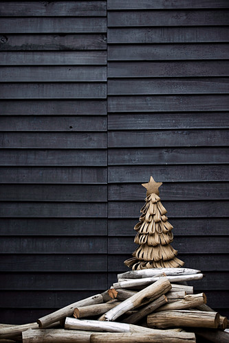 Stylized Christmas tree made of jute loops and driftwood sticks in front of a wooden wall on a terrace