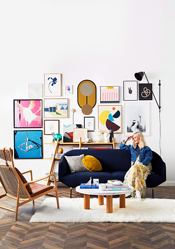 Blond woman sitting on blue sofa, framed artwork on wall