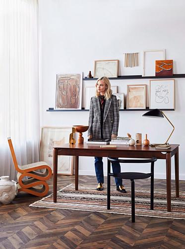 Junge Frau hinter Schreibtisch, gerahmte Kunstwerke auf Regalen
