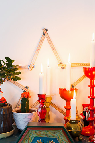 Christmas arrangement with star made from folding ruler and lit candles