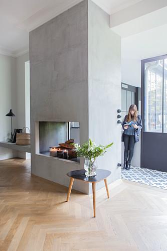 Coffeetable vor Kamin, im Hintergrund Frau an der Tür