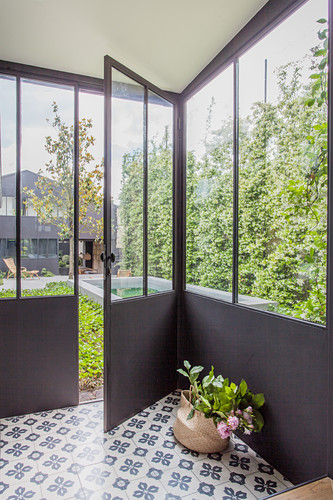 Glazed area with cement floor tiles and French windows leading into garden