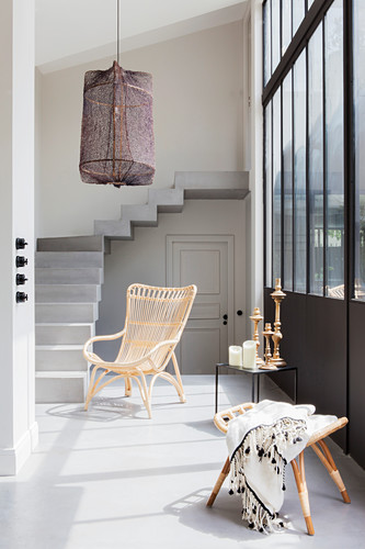 Rattan armchair, side table and stool below window