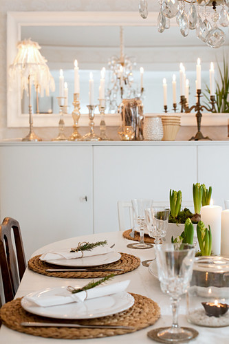 View across set dining table to tall sideboard with Christmas decorations in Scandinavian dining room