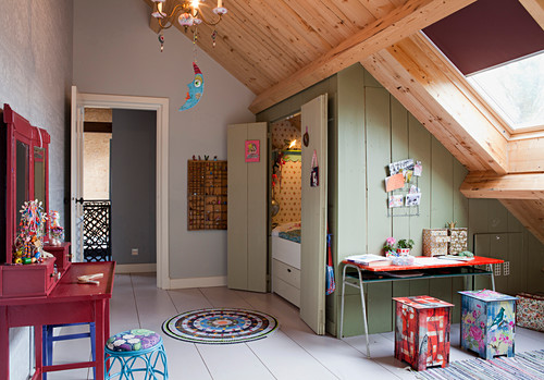 Alcove bed below sloping ceiling in colourful, rustic child's bedroom