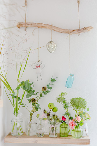 Twigs and flowers in various vases below ornaments hung from branch