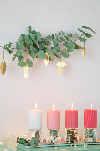 Eucalyptus branches with gold pendants above arrangement of candles