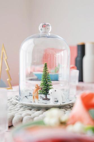 Winterlandschaft mit Dekotieren unter der Glashaube