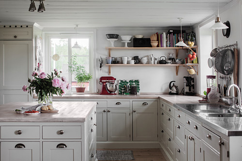 Panelled cabinets and shelves in pale country-house kitchen