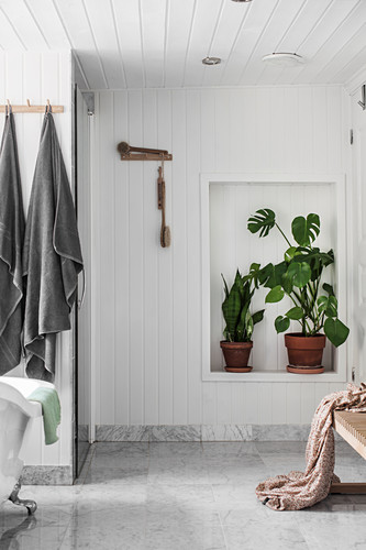 Houseplants in niche in bathroom with wood-panelled walls