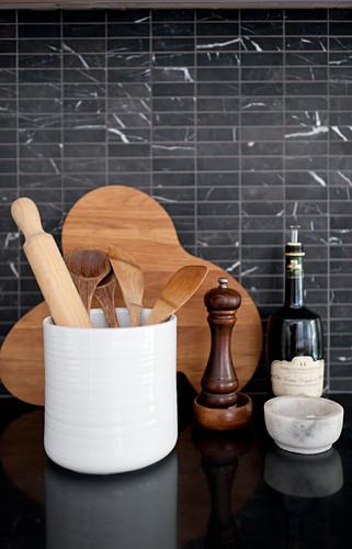Kitchen utensils, wooden board and pepper mill against black-tiled splashback