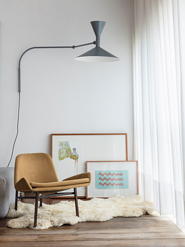 Designer chair on sheepskin rug, pictures leaning against wall and wall-mounted lamp next to window with floor-length curtains