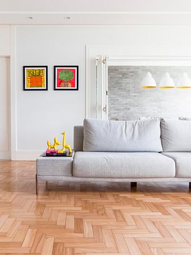 Pale grey sofa on herringbone parquet flooring