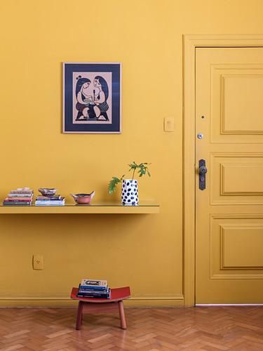 Yellow shelf on yellow wall next to yellow door