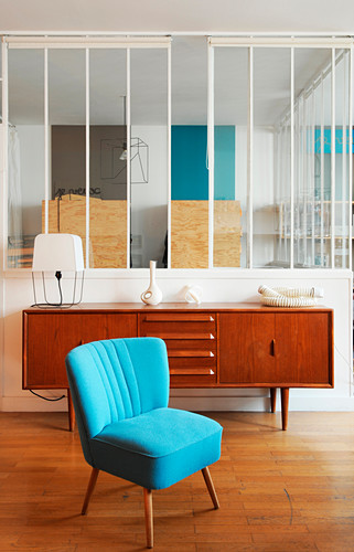 Blue easy chair and retro sideboard against glass partition wall