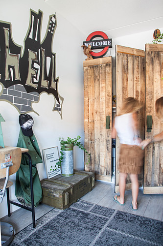 Wardrobe made from reclaimed wood and graffiti on wall in teenager's bedroom