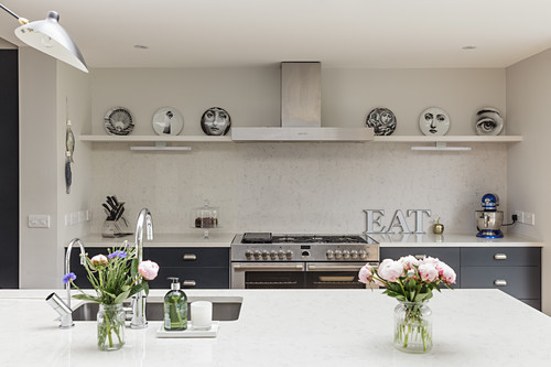 View past vases of flowers on island counter to kitchen counter
