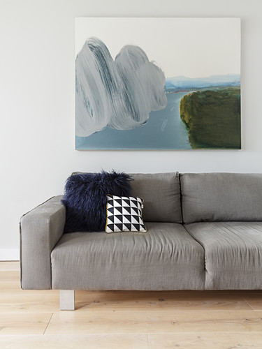 Scatter cushions on grey sofa below picture in living room
