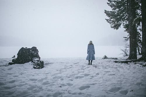 Frau in hellblauem Mantel am Ufer eines zugefrorenen Sees bei Schneefall
