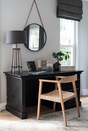 Black desk used as dressing table with round mirror and modern table lamp